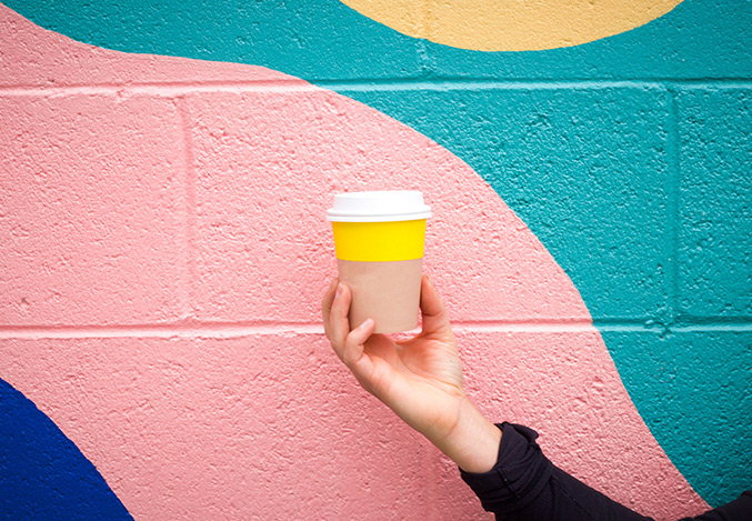 Colorful pastel wall with bright coffee cup in the foreground